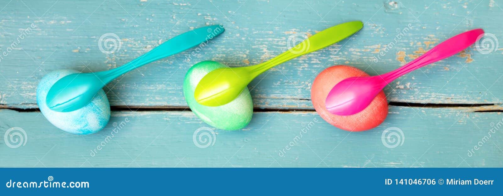 Trzy kolorowego farbującego Easter jajka i jajecznych łyżki na błękitnym drewnianym tle