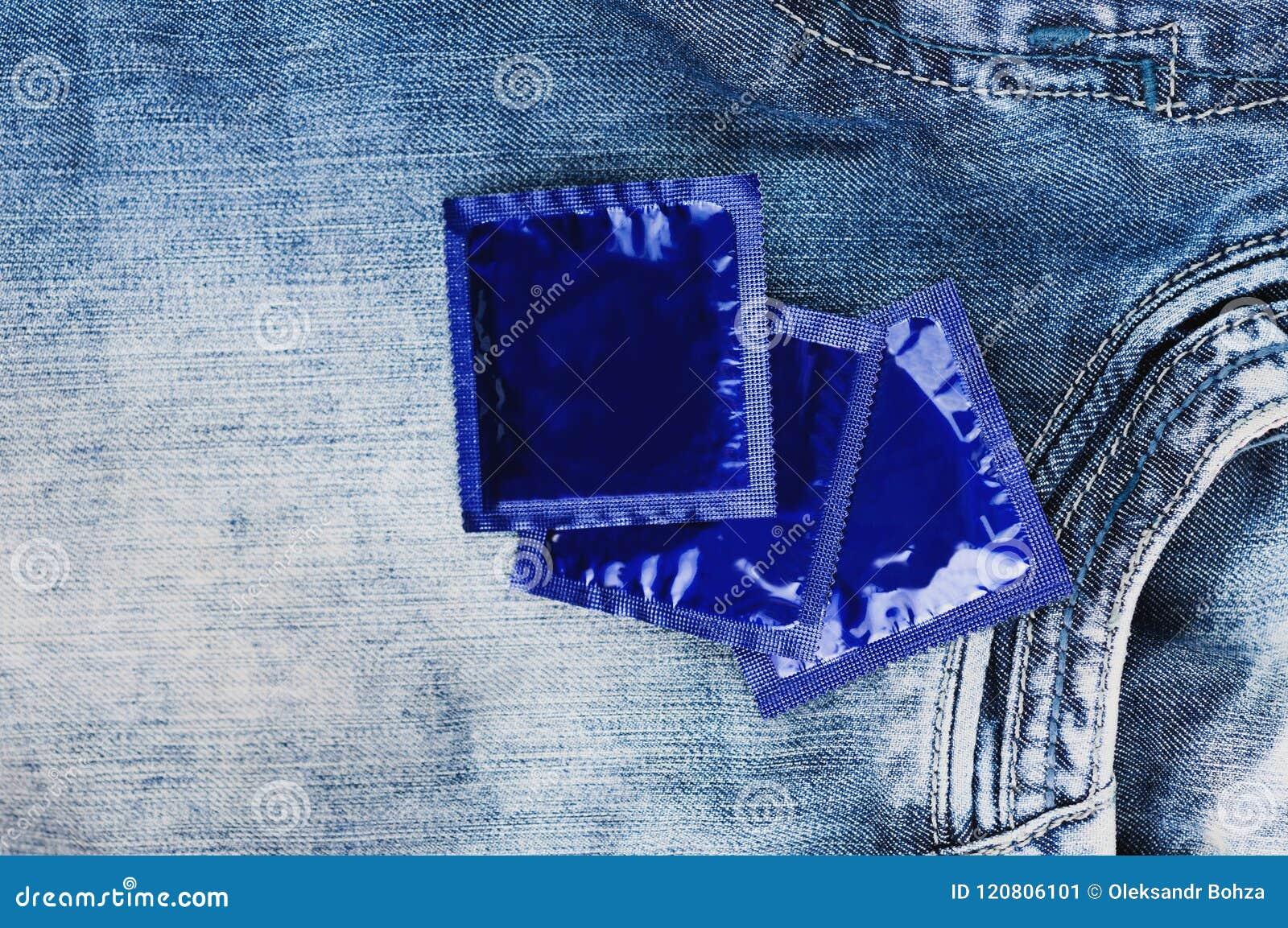 Trzy kondoma w foliowym błękitnym pakunku rozpraszali na niebieskich dżinsach
