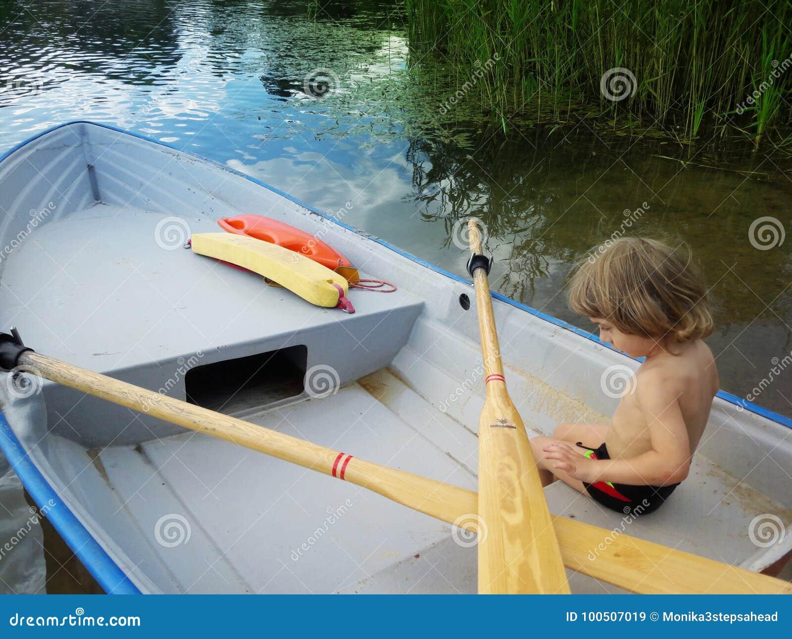 Trzy lat chłopiec na łodzi