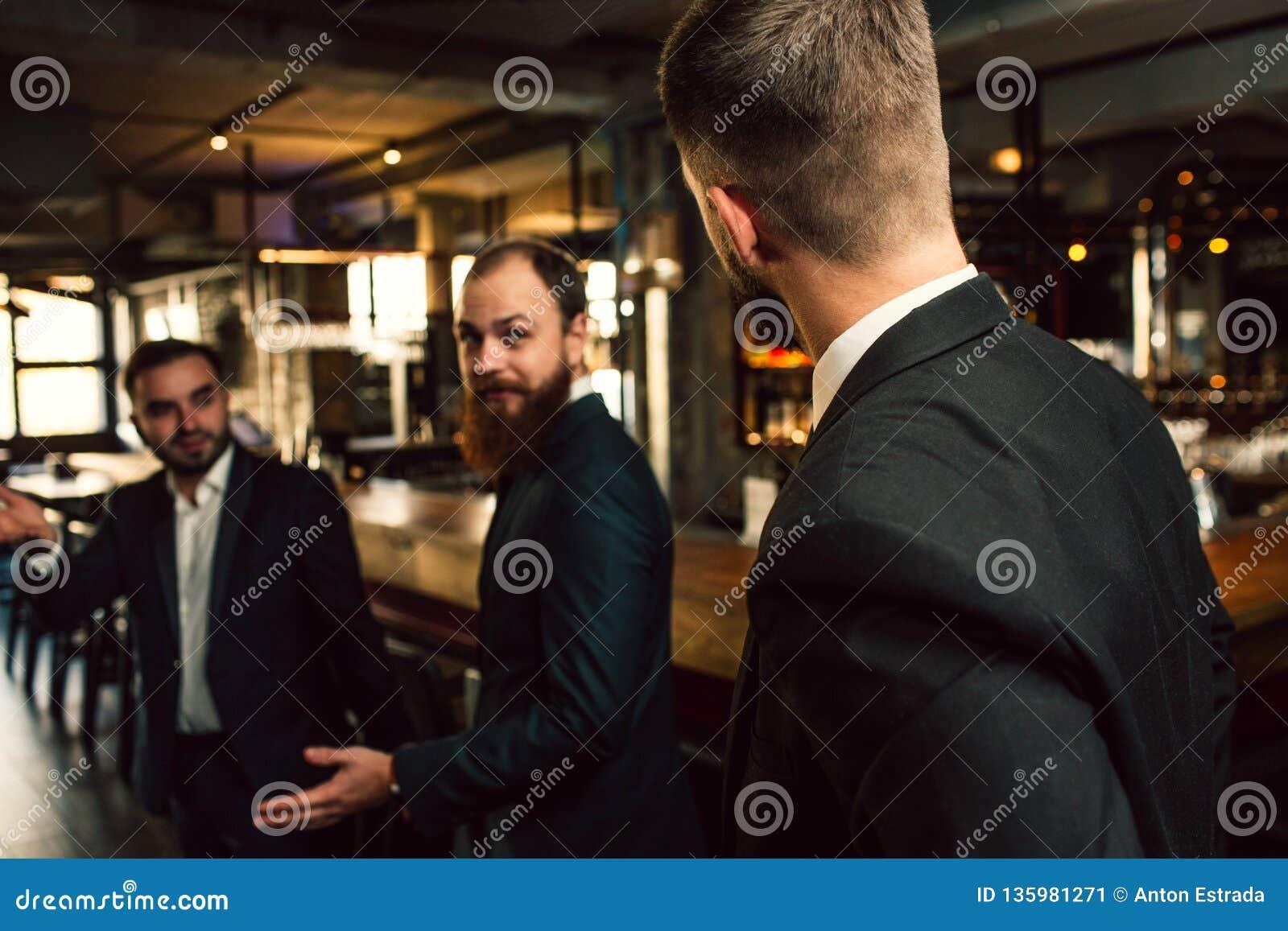 Trzy młodego człowieka w kostiumu loku przy each inny Jeden one statywowi z z powrotem kamera Urzędnicy stoją w pubie