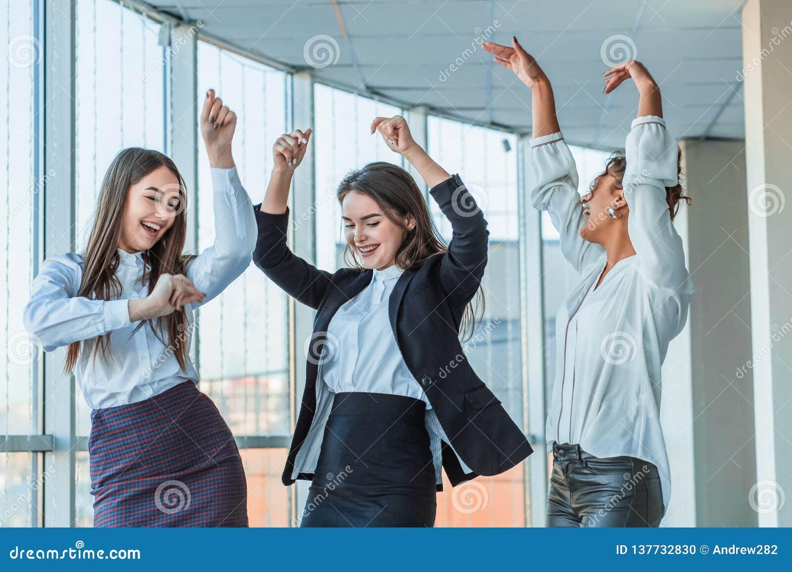 Trzy młodej pięknej brunetki biznesowej damy w biurze Wszystkie szczęśliwy dancingowy taniec z w górę kopii przestrzeni
