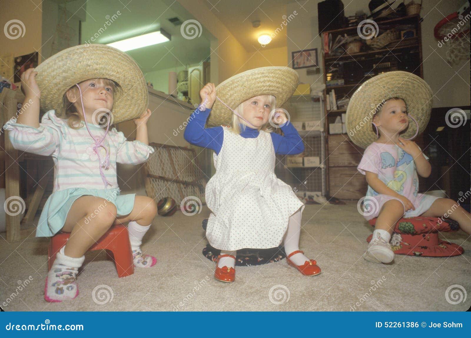 Trzy małej dziewczynki jest ubranym sombrero przy ich ośrodkiem opieki dziennej, Waszyngtoński d C