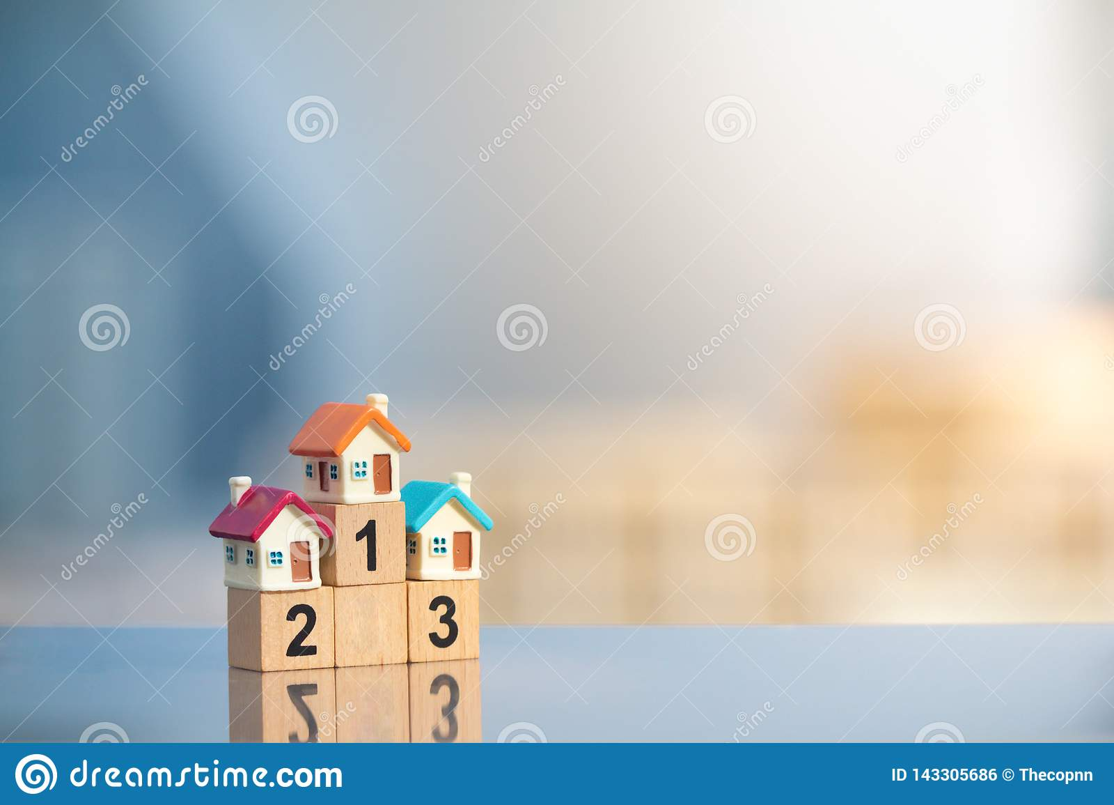 Trzy miniaturowego domu na pierwszy miejscu zwycięzcy podium na nowożytnym miasta tle