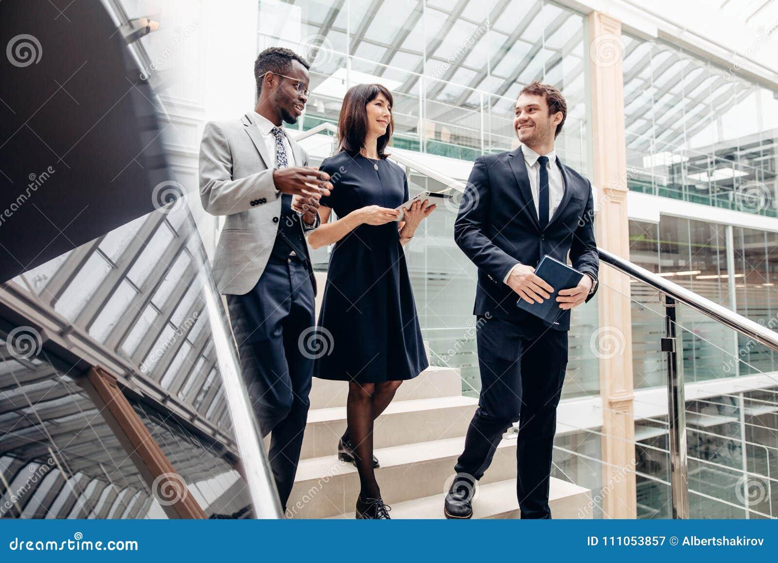 Trzy multiracial ludzie biznesu chodzi w dół na schodkach z cyfrową pastylką