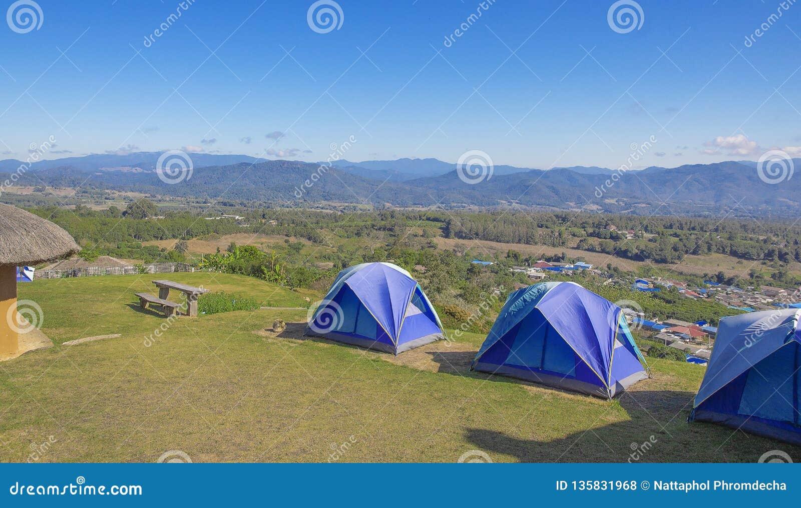 Trzy namiotu błękit na wysokich wzgórzach Tło góra i niebieskie niebo