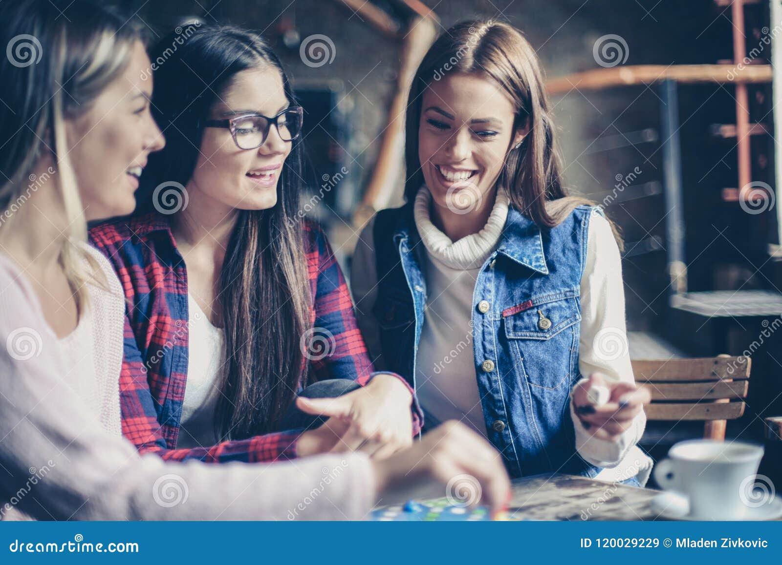 Trzy one uśmiechają się rozochoconej dziewczyny bawić się grę planszowa
