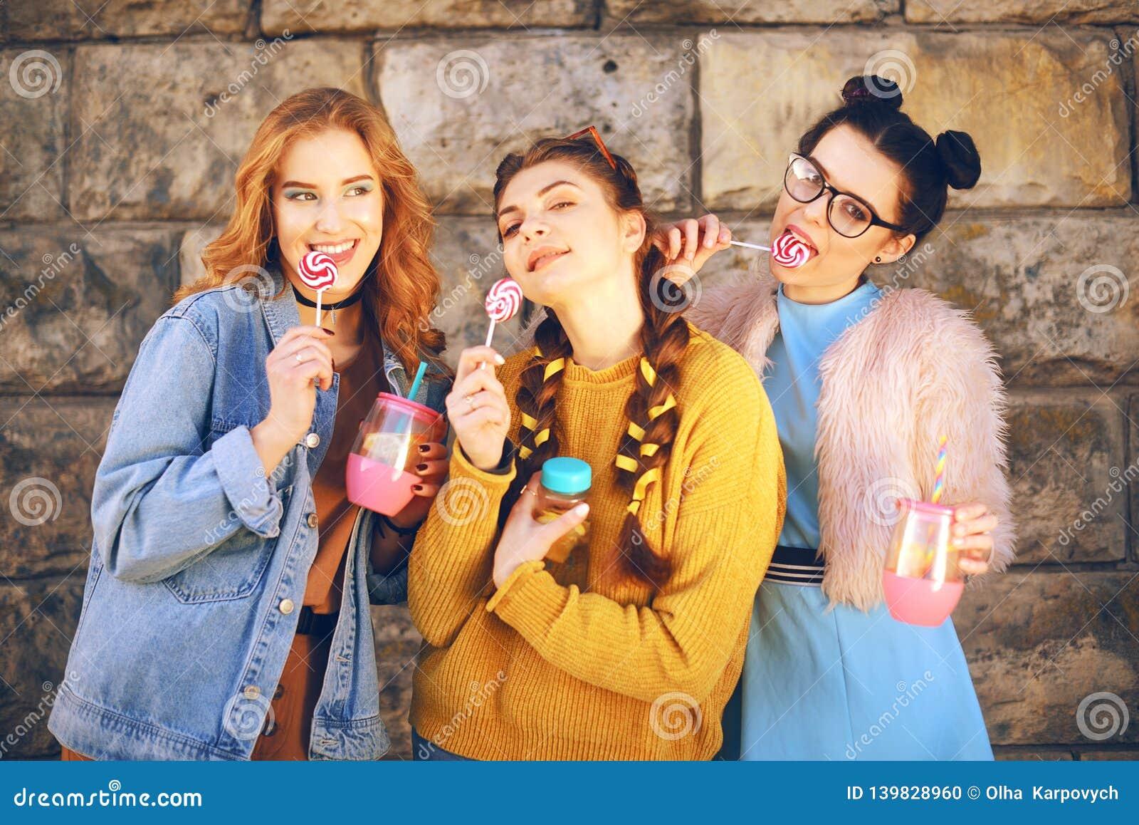 Trzy pięknej dziewczyny jedzą lizaki i napoju lemonad w menchii butelce Dziewczyny z różnymi fryzurami Przyjaciele, kobieta