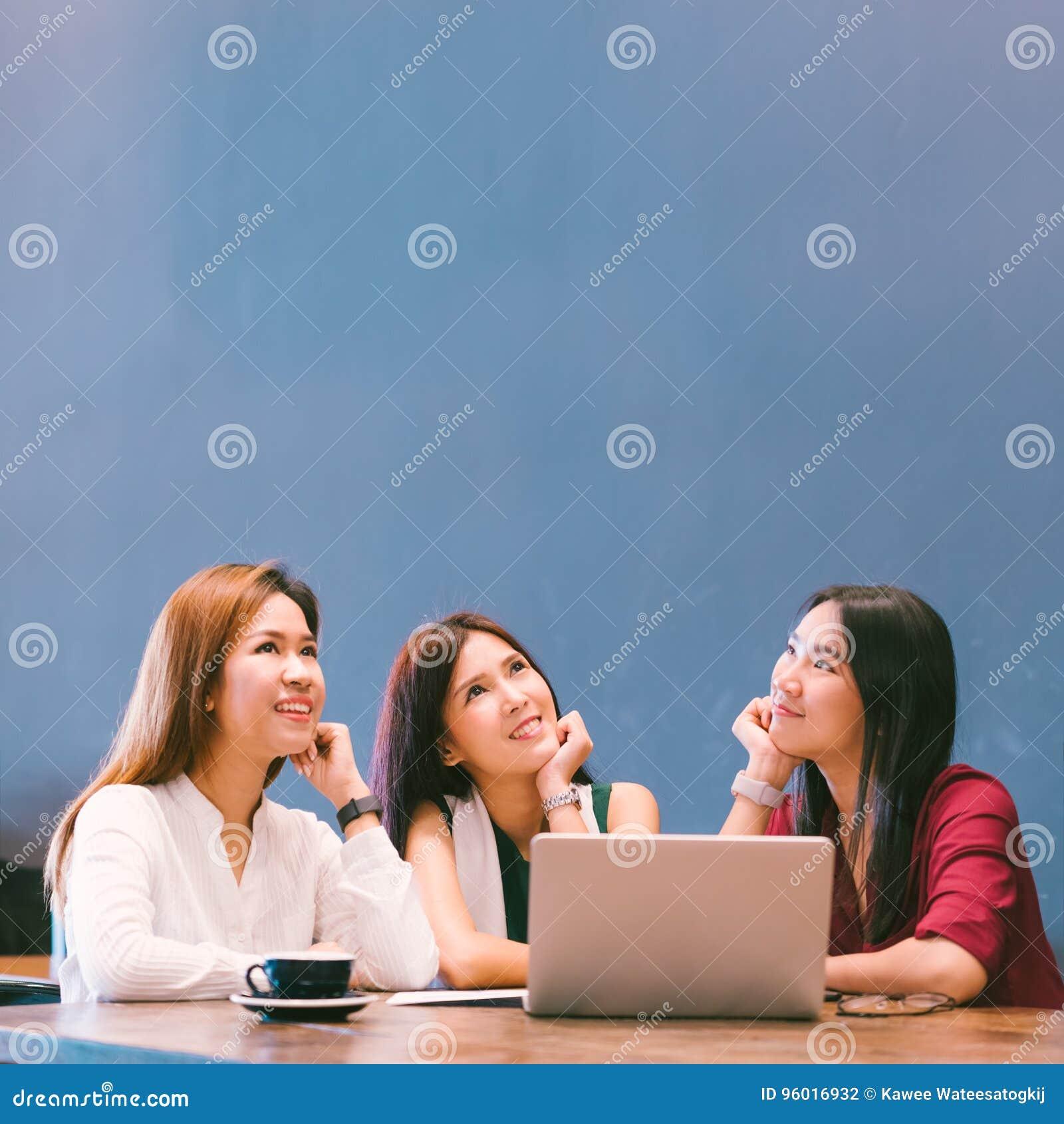 Trzy pięknej Azjatyckiej dziewczyny patrzeje oddolny kopiować przestrzeń podczas gdy pracujący przy kawiarnią
