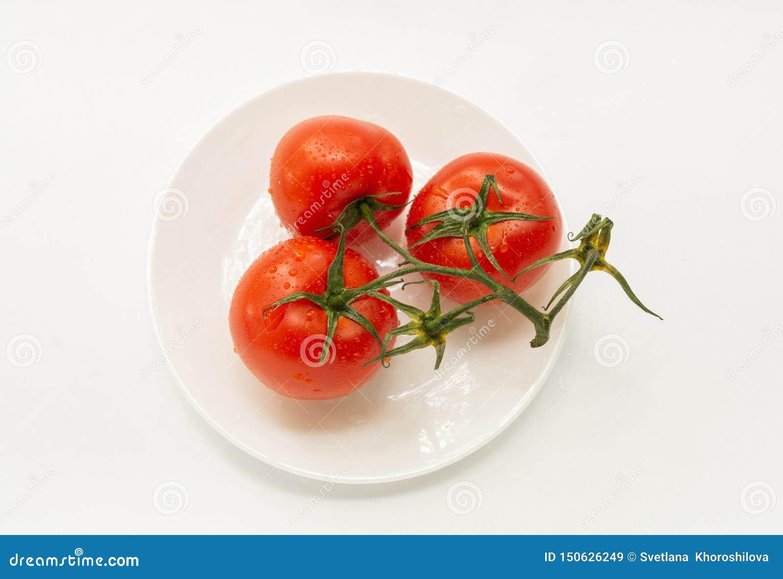 Trzy pomidoru na białym talerzu, izolator