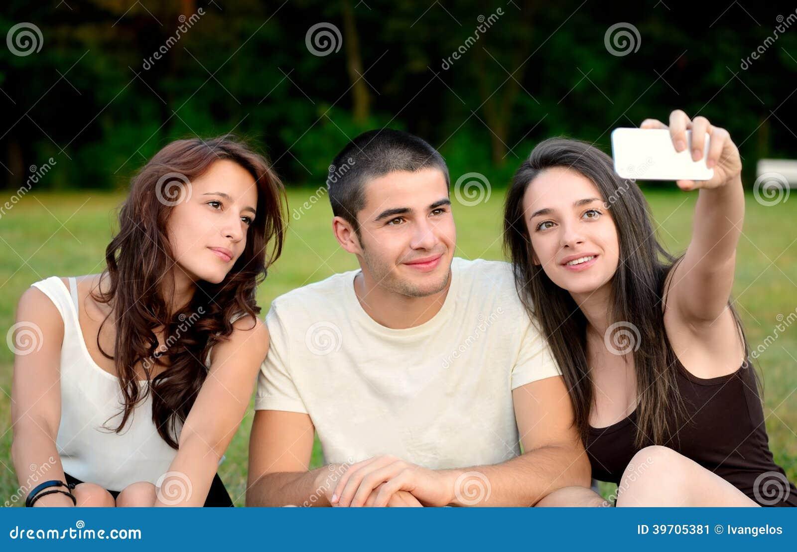 Trzy przyjaciela bierze fotografie outside i uśmiechnięte