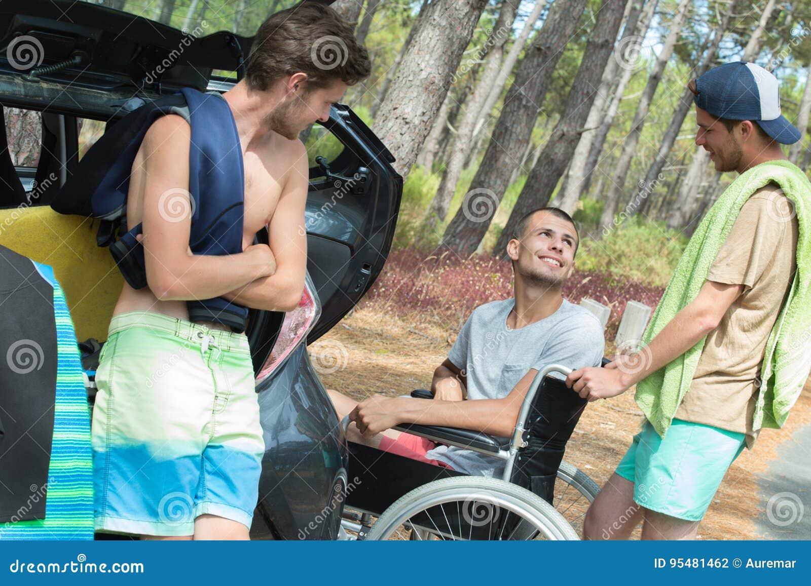 Trzy przyjaciela przyjeżdża przy plażą jeden handicaped