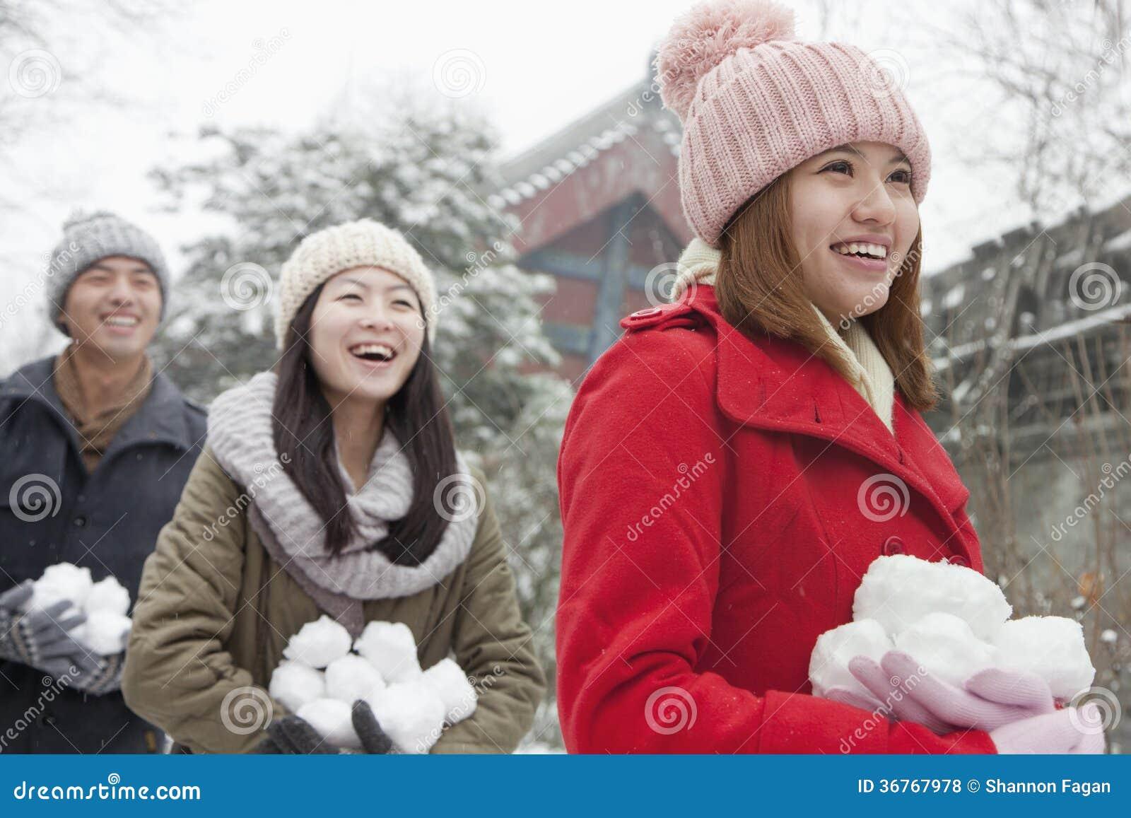 Trzy przyjaciela Trzyma śnieżne piłki w śniegu w parku