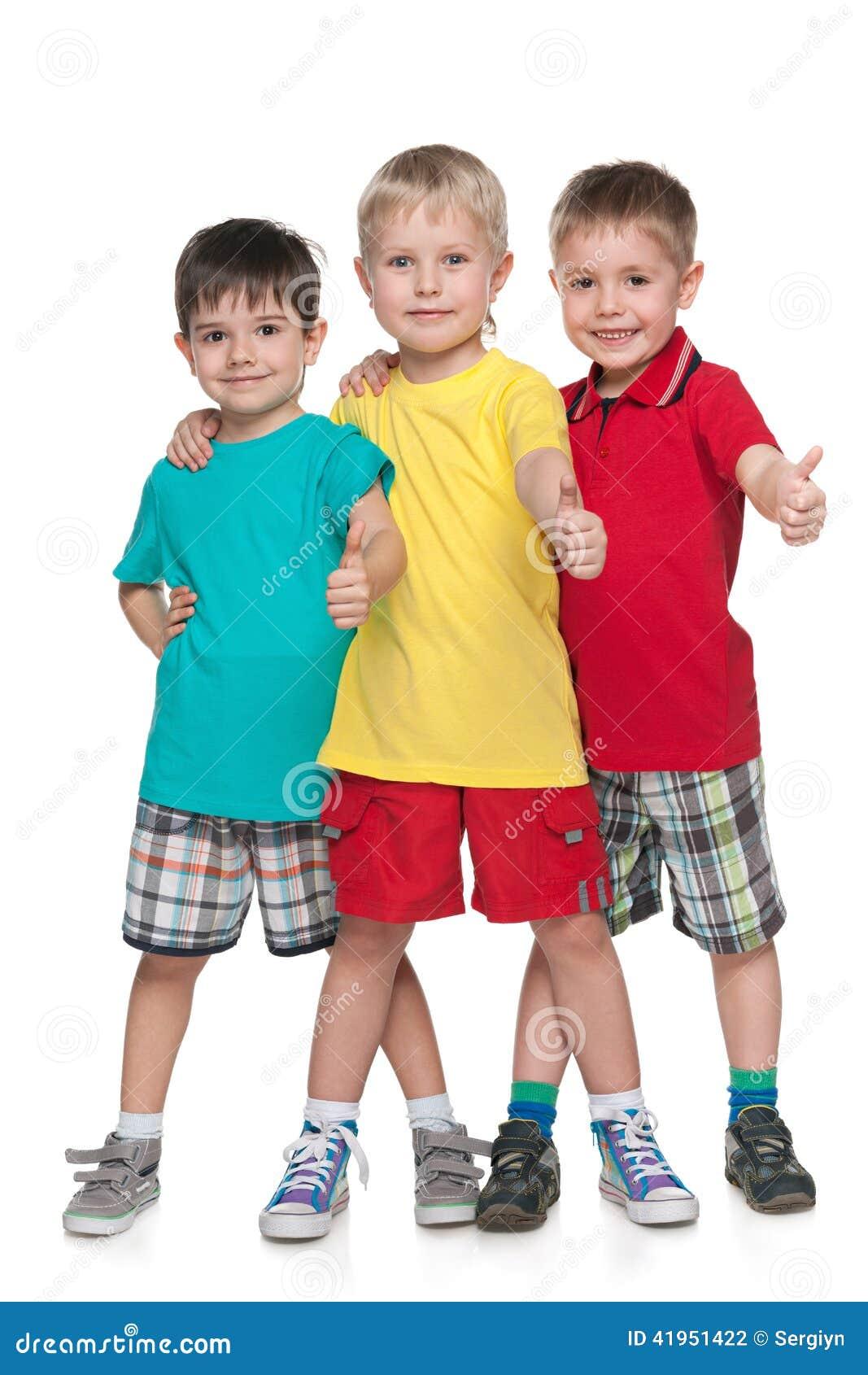 Trzy rozochoconej chłopiec trzymają jego aprobaty