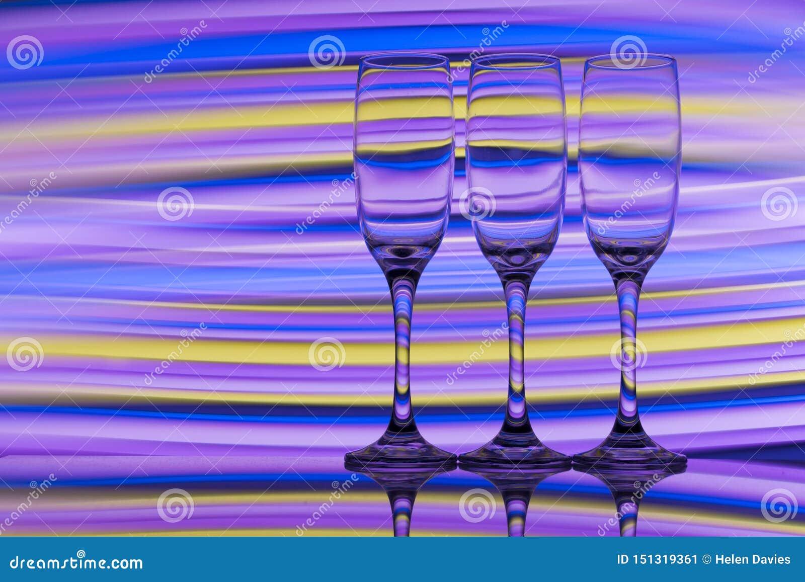 Trzy szampańskiego szkła z tęczą kolorowy lekki obraz za one z rzędu