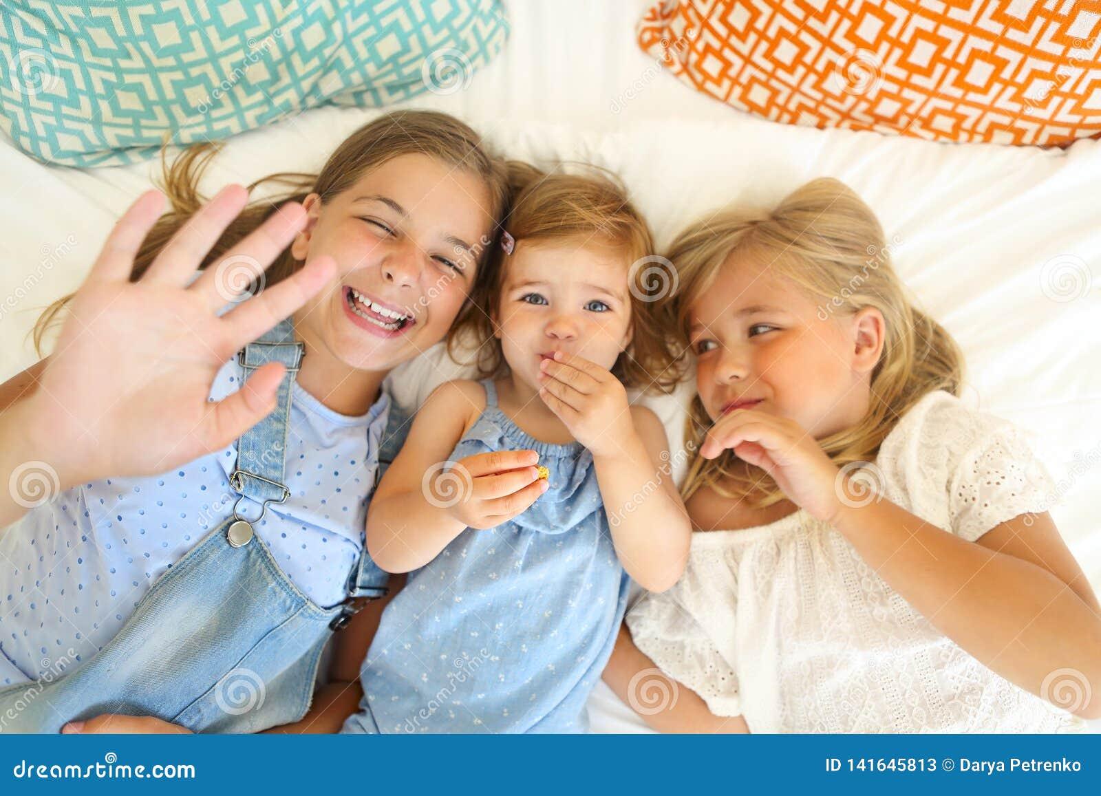 Trzy szczęśliwej małej siostry na łóżkowym mieć zabawę