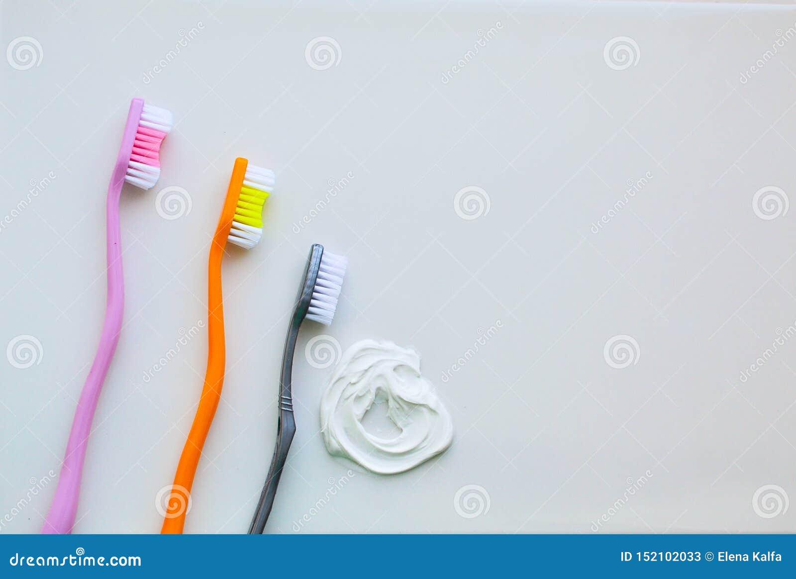Trzy toothbrushes na białym tle białej pascie do zębów i Pojęcie stomatologiczna higiena, osobista opieka