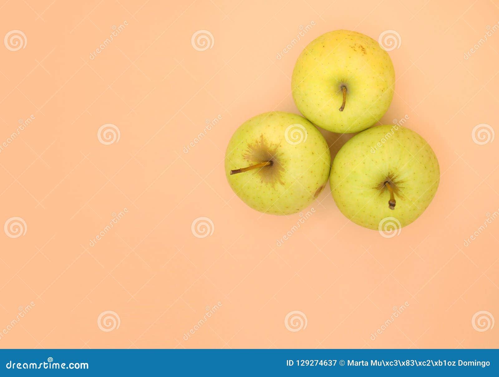 Trzy złotego zielonego jabłka na świetle - pomarańcze powierzchnia