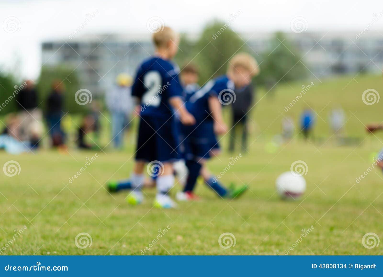 Trzy zamazującego piłka nożna dzieciaka