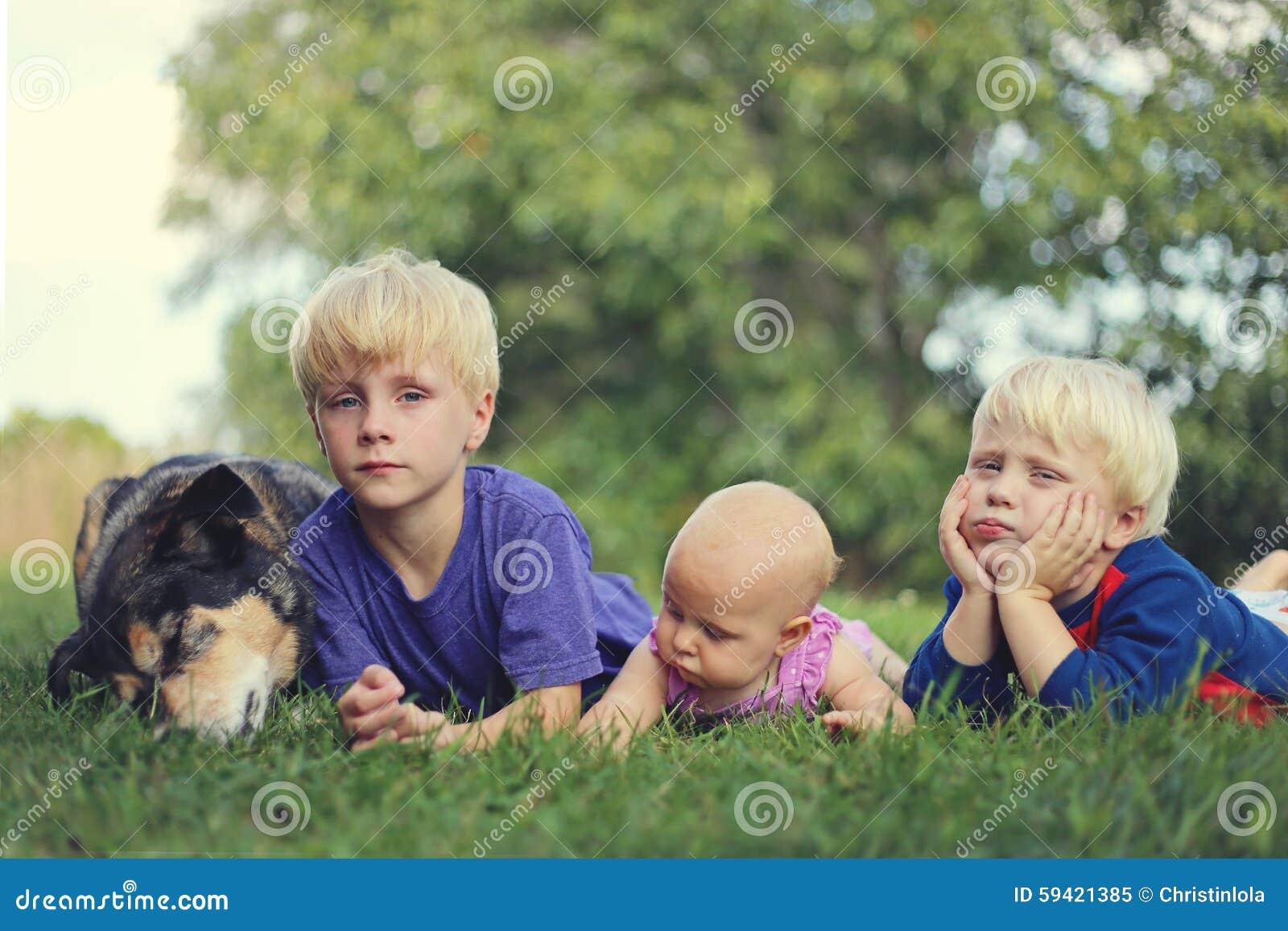 Trzy Zanudzającego młodego dziecka i Psiego Relaksującego Outside