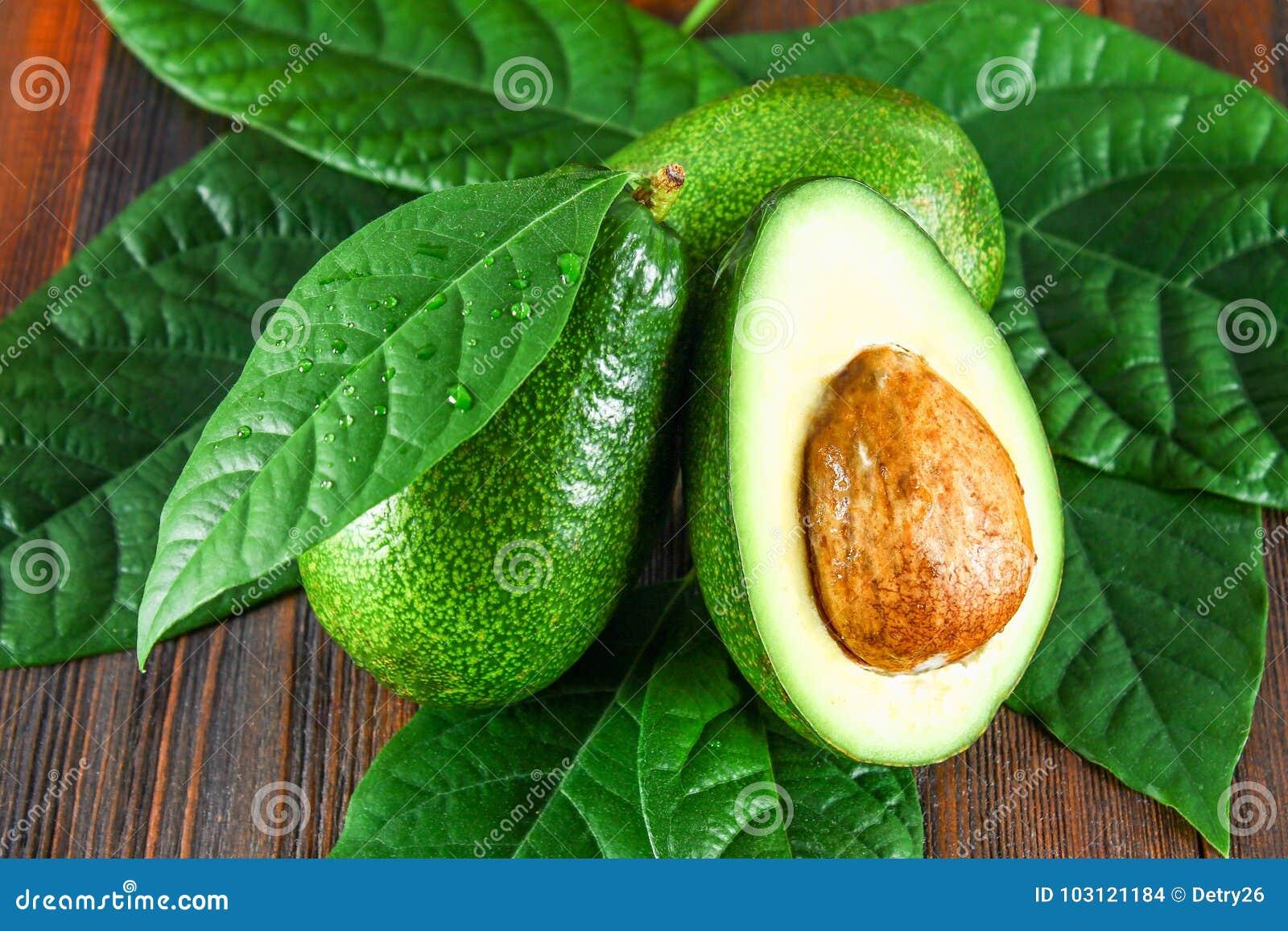 Trzy zielonej surowej dojrzałej avocado owoc i rżniętej połówka z kością z liśćmi na brown drewnianym stole