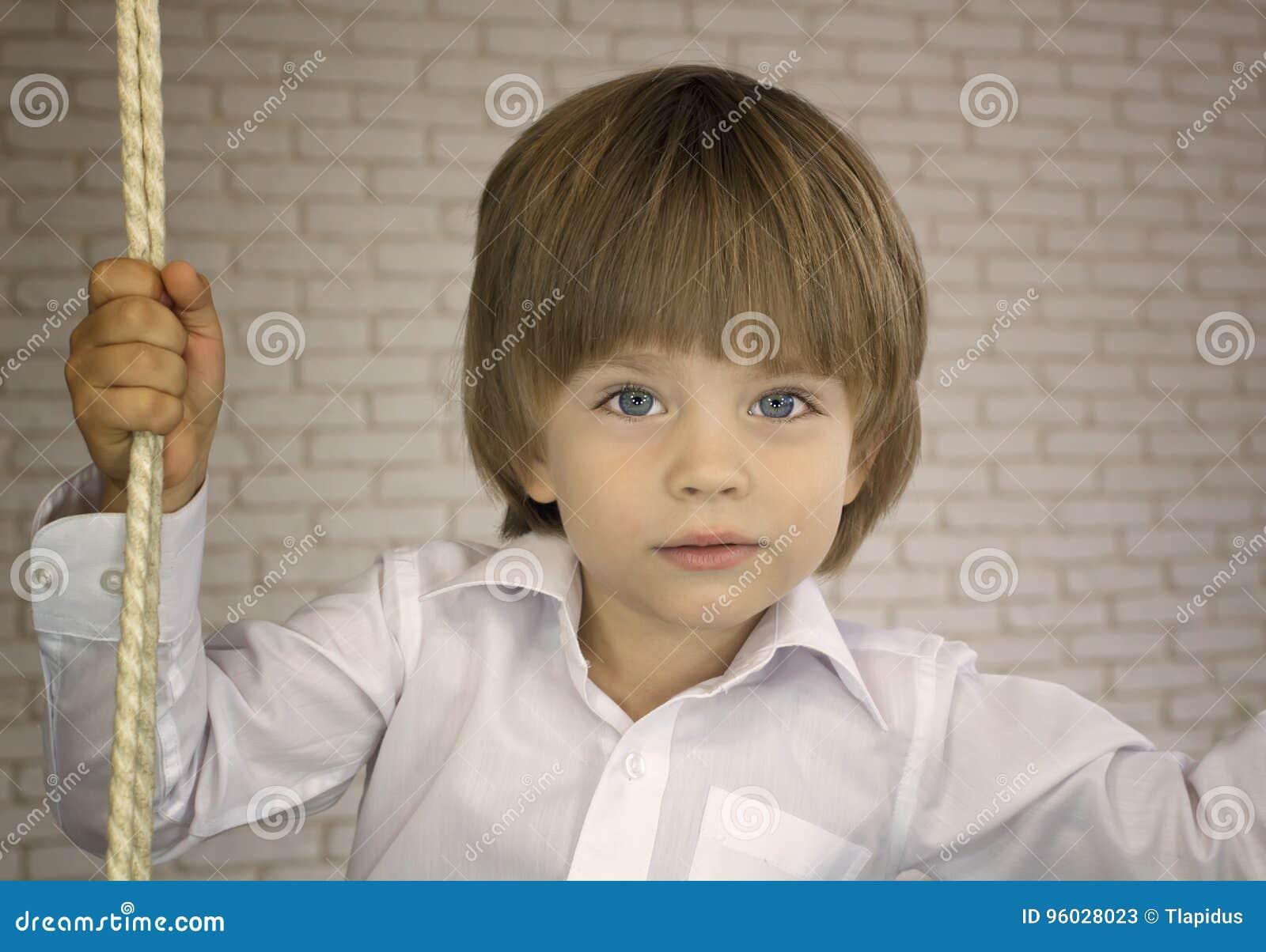 Trzyletnia chłopiec w białej koszula z arkaną