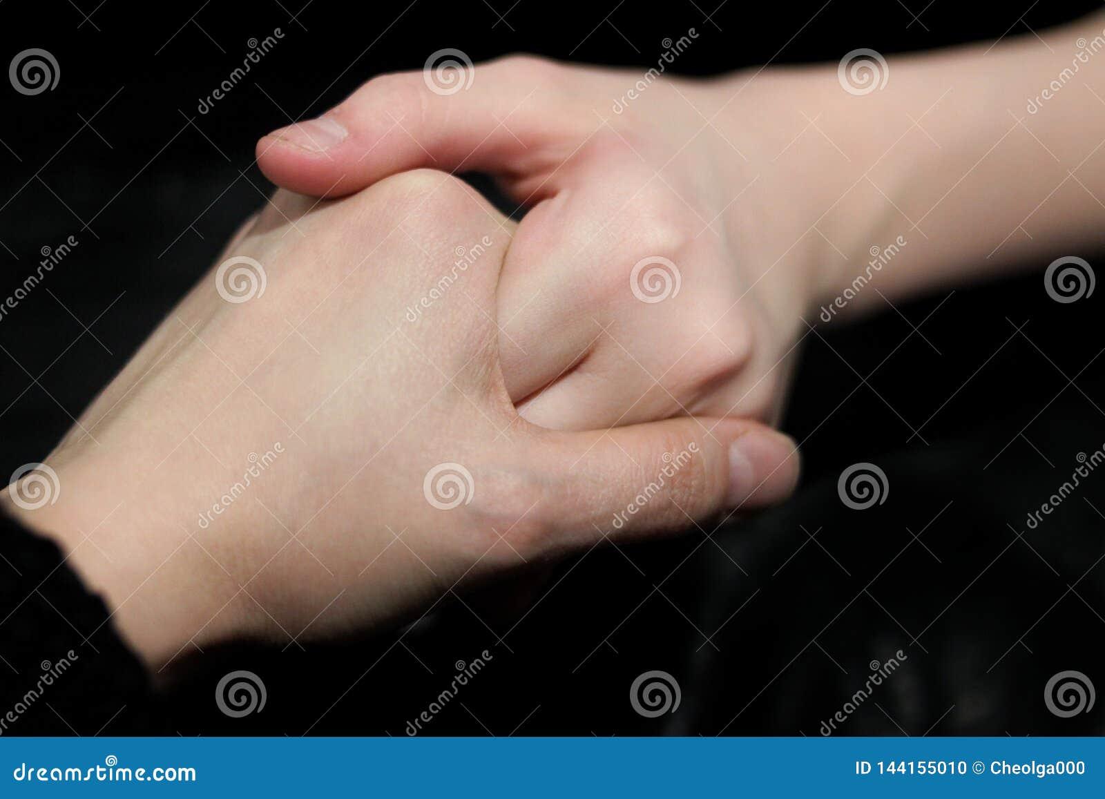 Trzymający za pomocnej dłoni ręki dwa ludzie, jeden pomaga inny, przeciw ciemnemu tłu