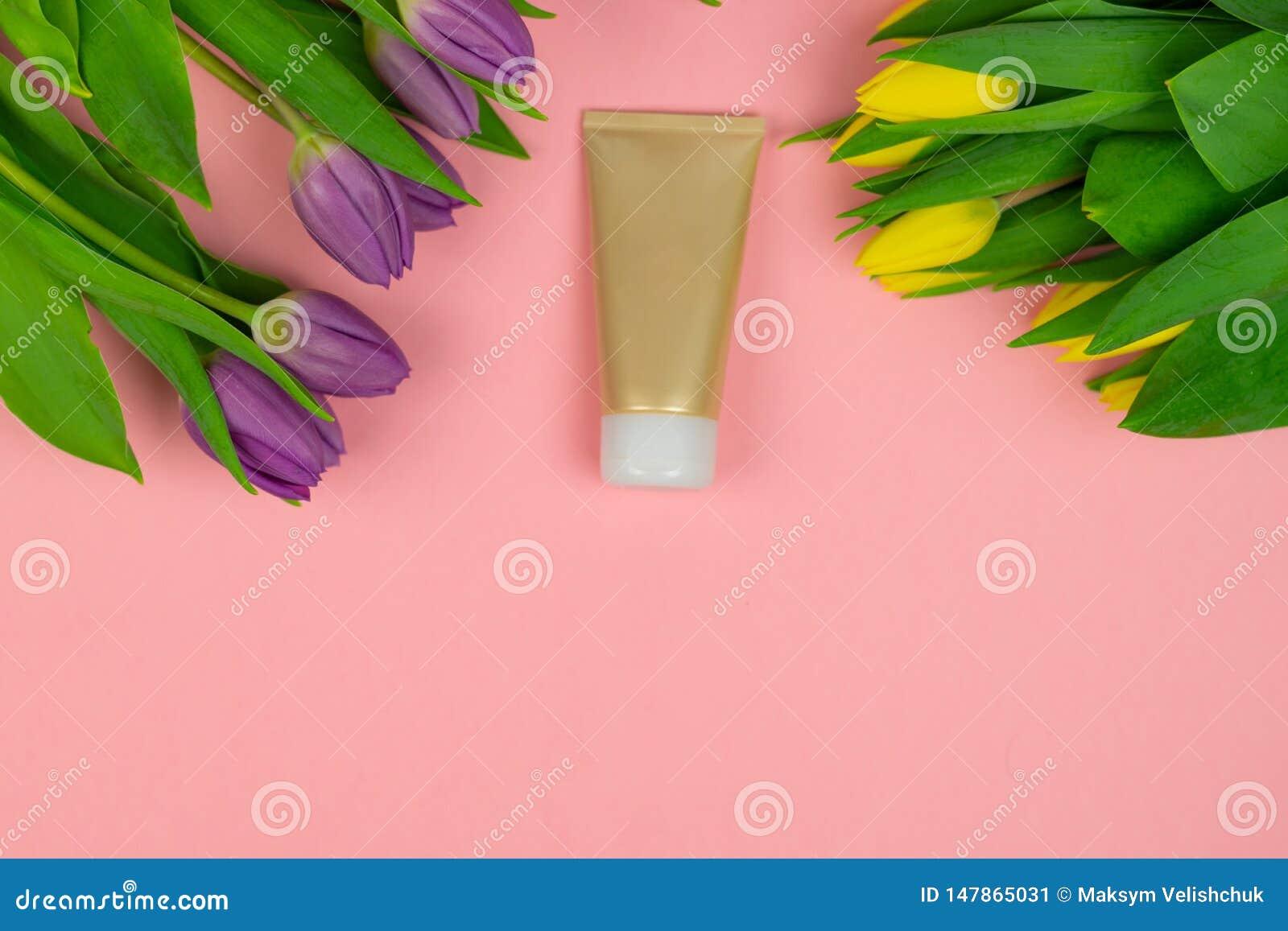 Tube vide de cr?me sur un fond rose avec des fleurs