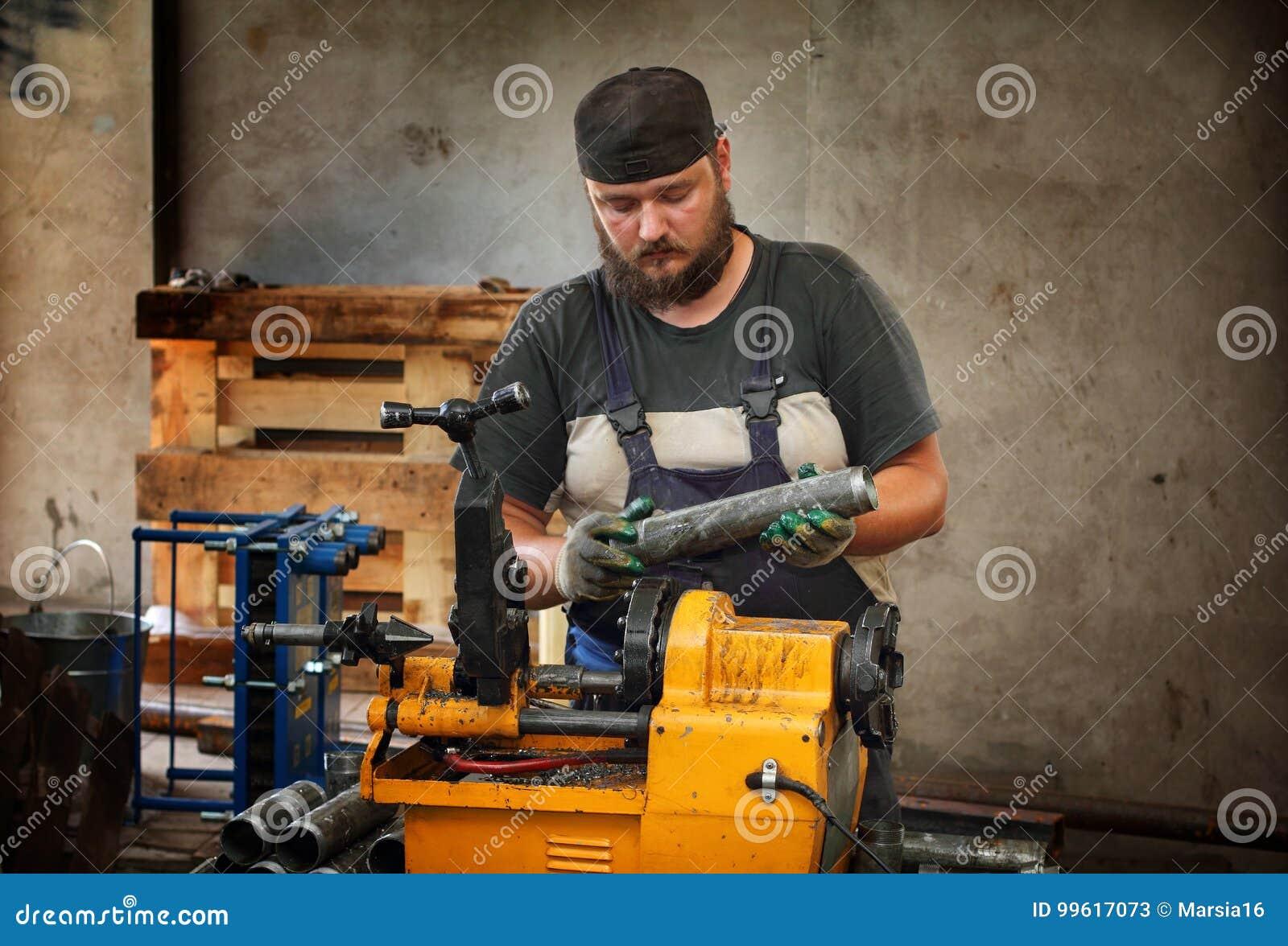 Tubería de acero del corte del trabajador con la máquina para roscar