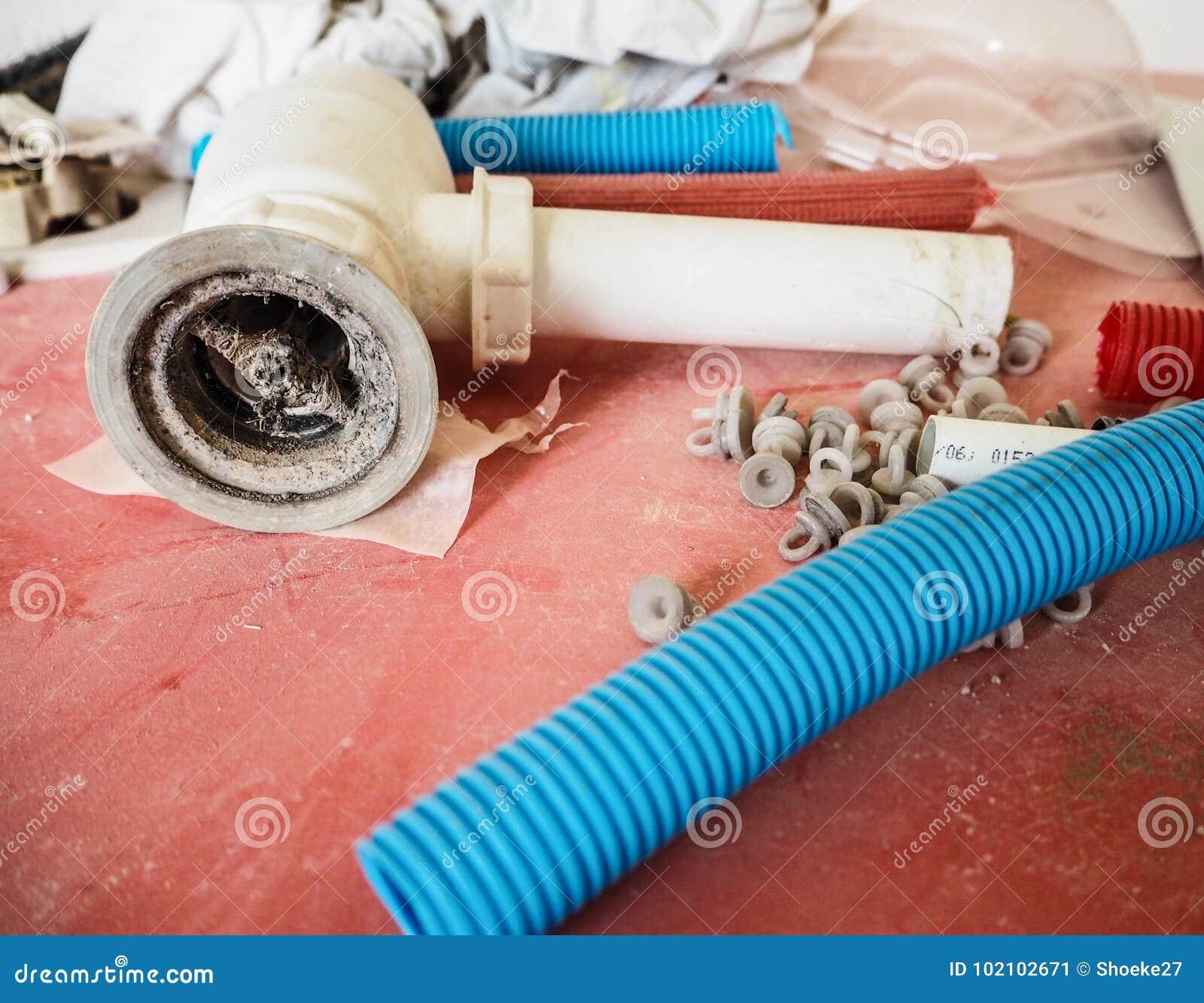 Tubes en plastique, prises et drain obstrué sur une table rouge