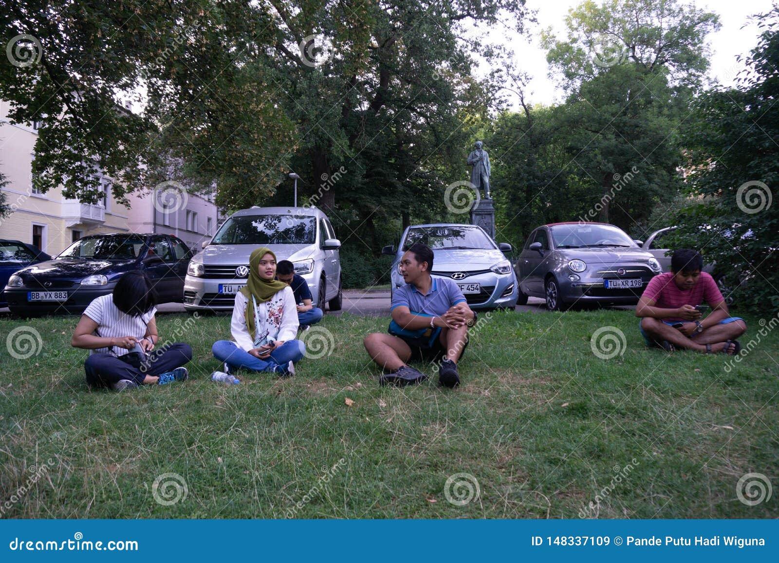 TUBINGEN/GERMANY-, 31. JULI 2018: Einige asiatische Touristen sa?en auf dem Rasen, nahe dem Parkplatz und miteinander sprachen