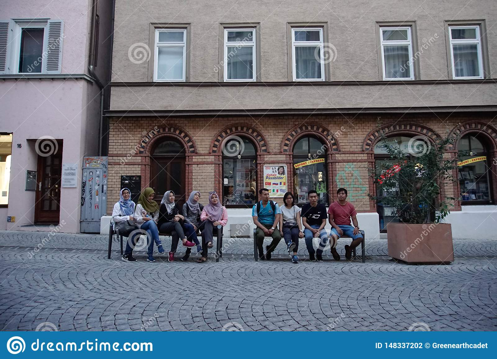 TUBINGEN/GERMANY-JULY 31 2018: some Asian Muslim tourists are sitting on a bench near the pedestrian street around the city of