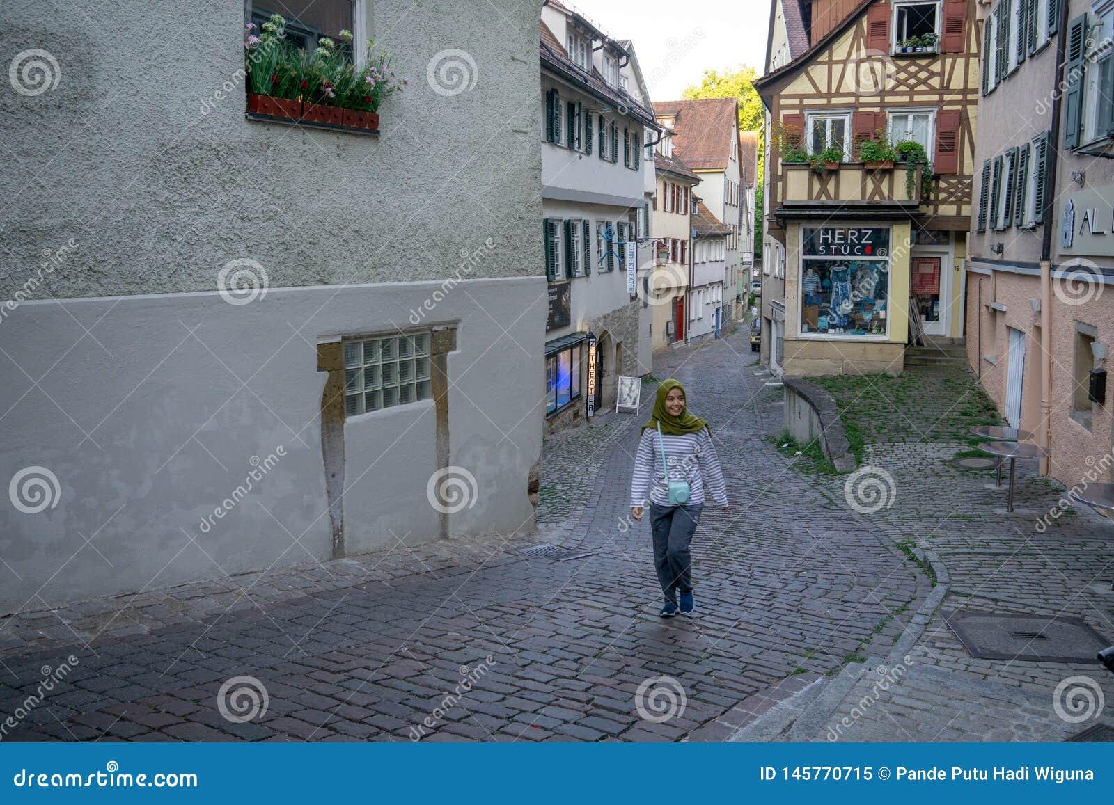 TUBINGEN/GERMANY- 30 LUGLIO 2019: Una ragazza musulmana che cammina sul percorso vicino Nizza alle vecchie case a graticcio del f
