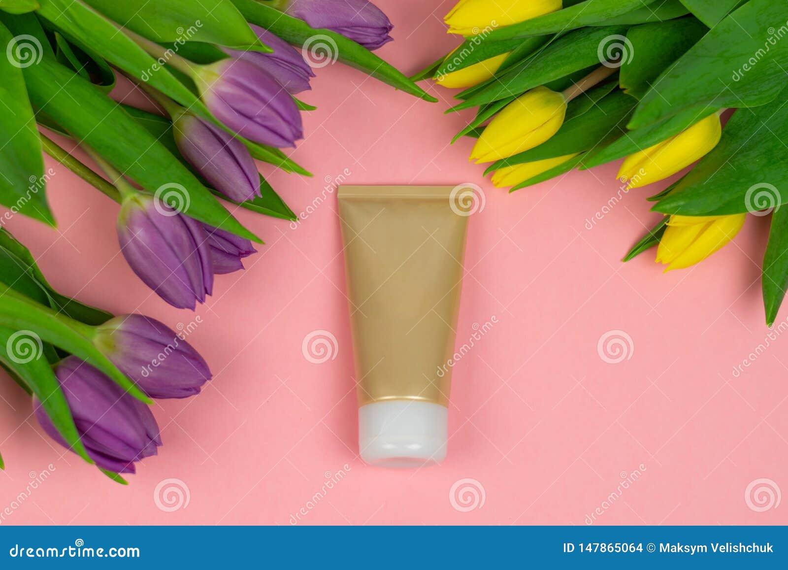 Tubo vac?o de la crema en un fondo rosado con las flores