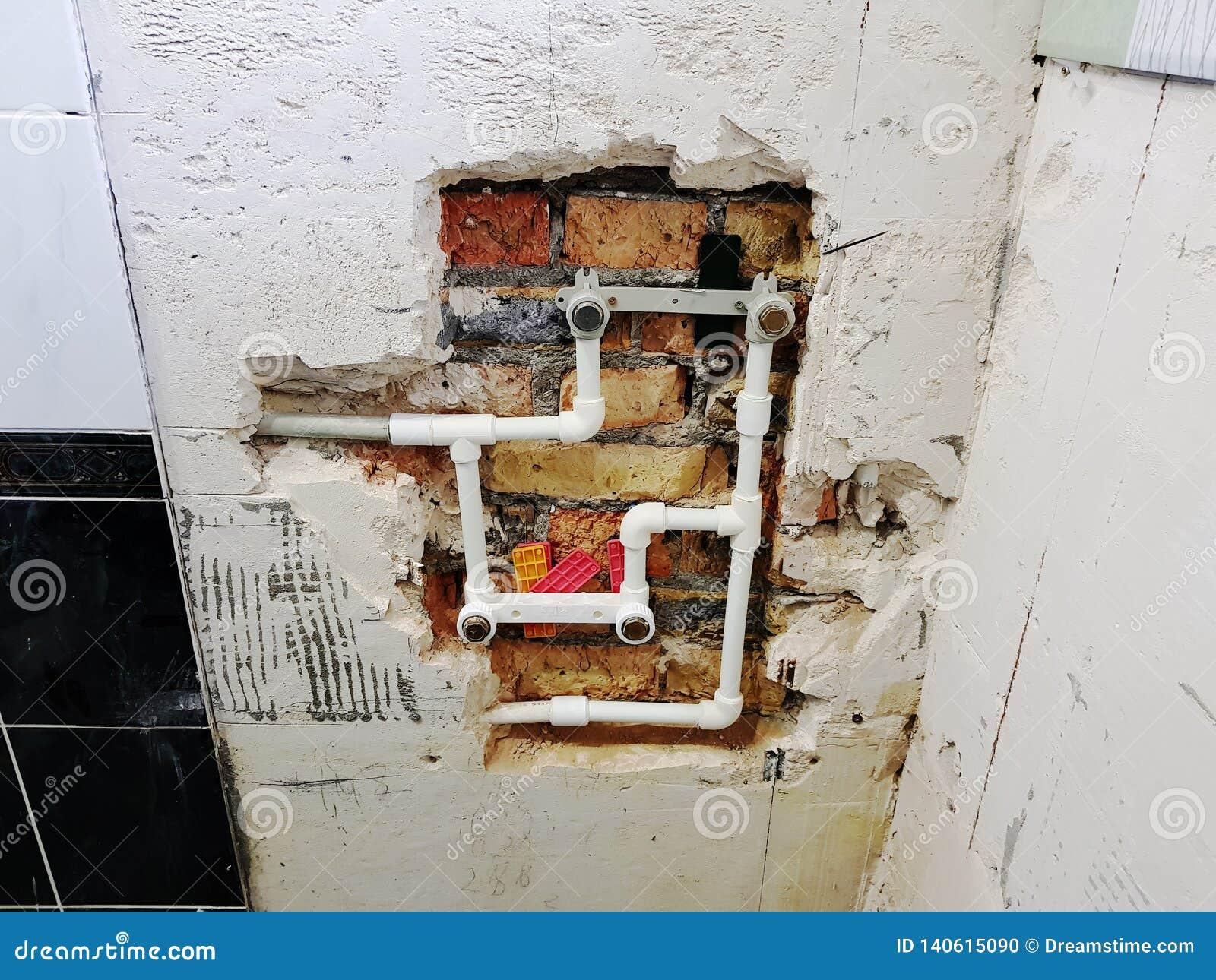 Tubo y puertas del propileno en una pared de ladrillo - soldadura del propileno