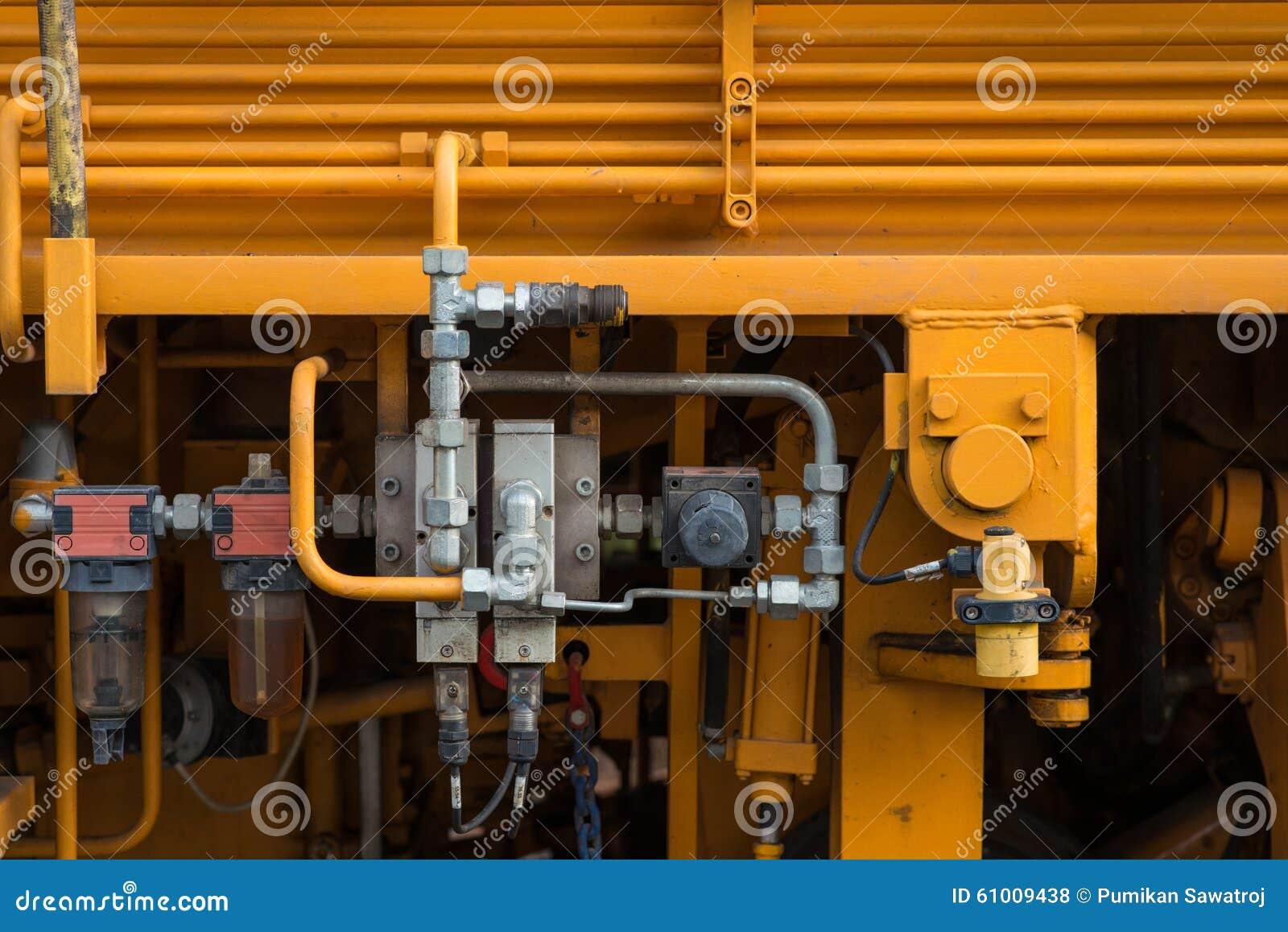 Tubos, encaixes e alavancas hidráulicos no painel de controle do levantamento