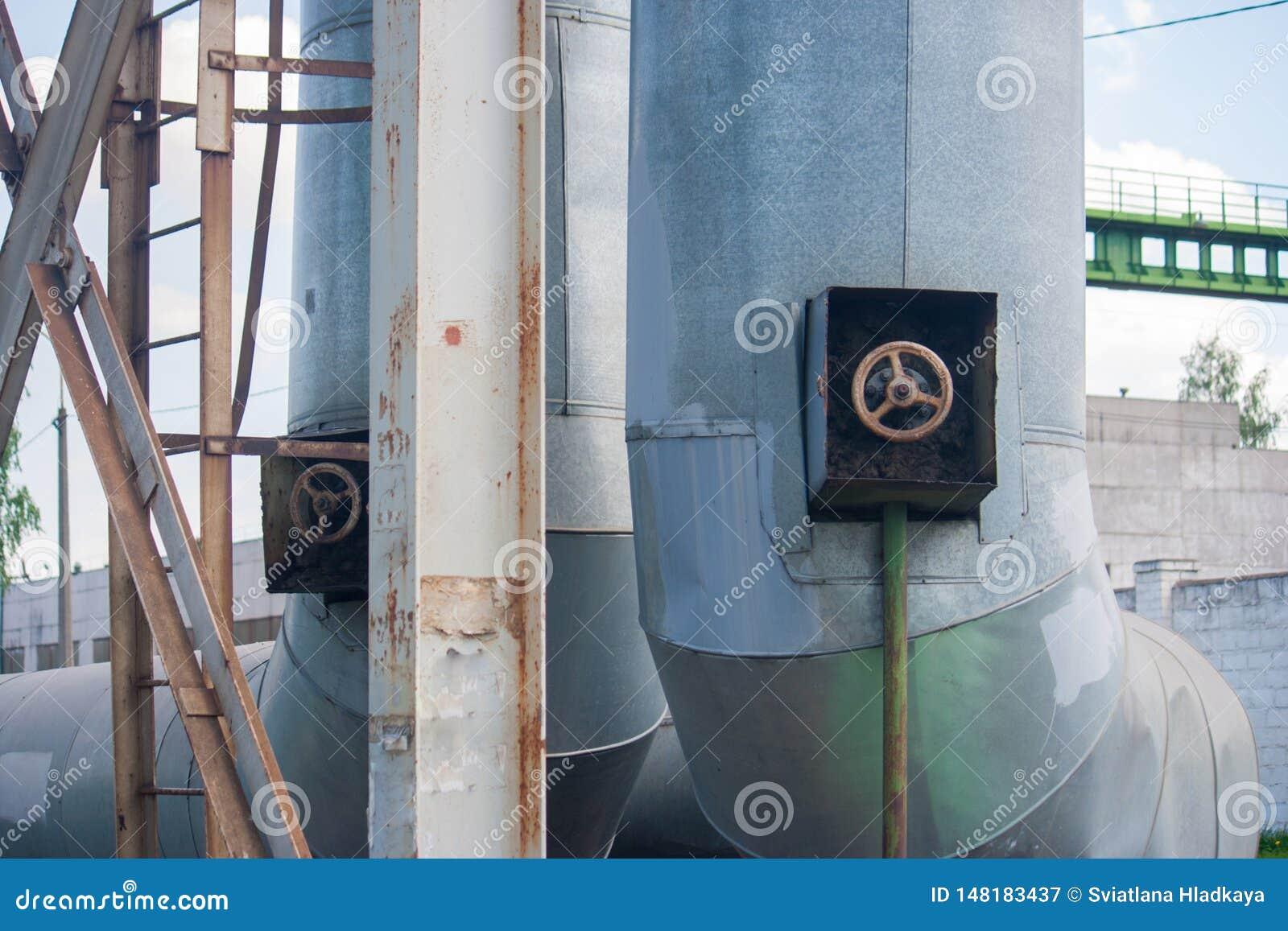 Tubos industriales del metal grueso con las válvulas y el primer de las escaleras