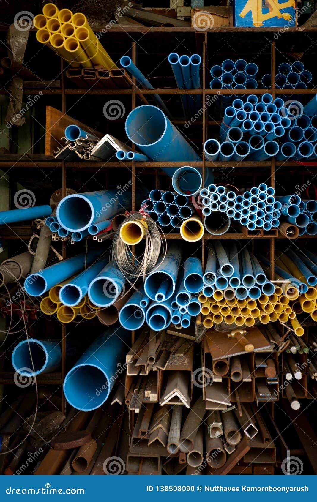 Tubulações azuis e amarelas do PVC no armazém
