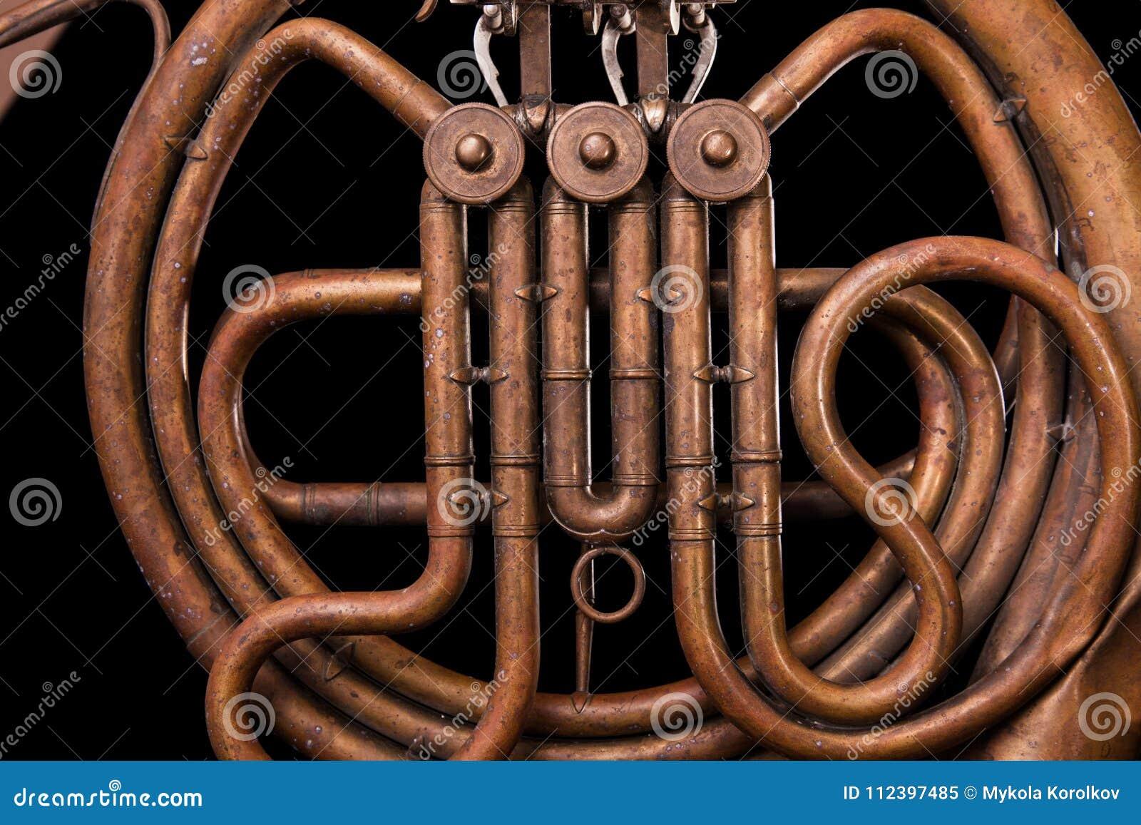 Tubulações de bronze do vintage, válvula, trompa francesa mecânica chave dos elementos, fundo preto Bom teste padrão, instrumento