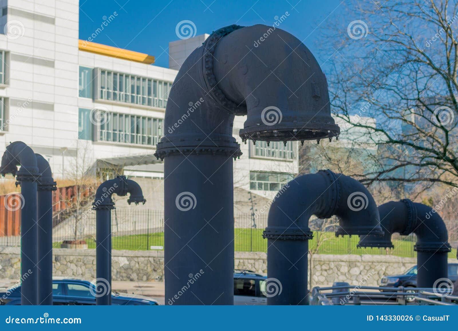 Tubulações industriais cinzentas grandes, colando fora da terra