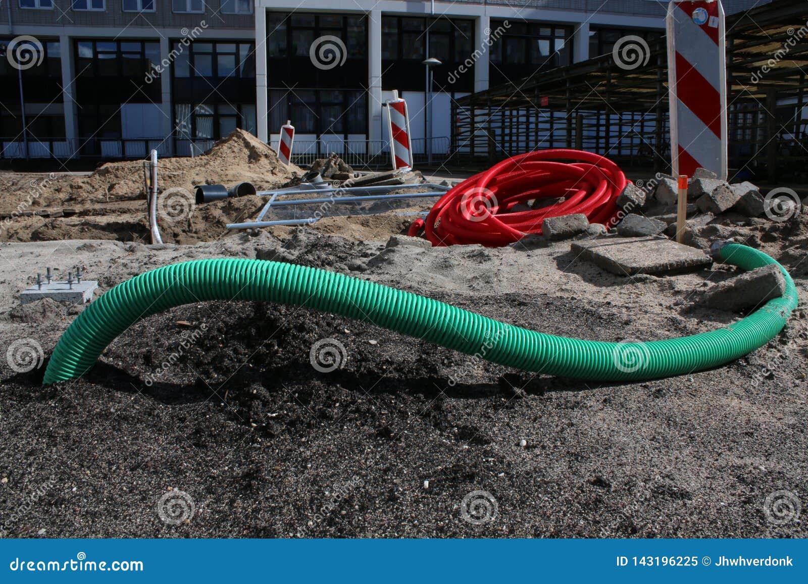 Tubulações outros materiais que colocam na terra em um canteiro de obras inacabado