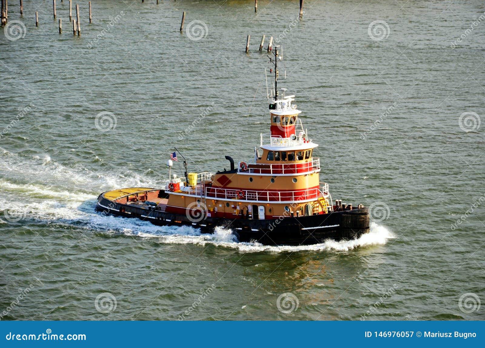 Tugboat που πλέει για να βοηθήσει με την προσόρμιση του σκάφους φορτίου, κόλπος της Νέας Υόρκης