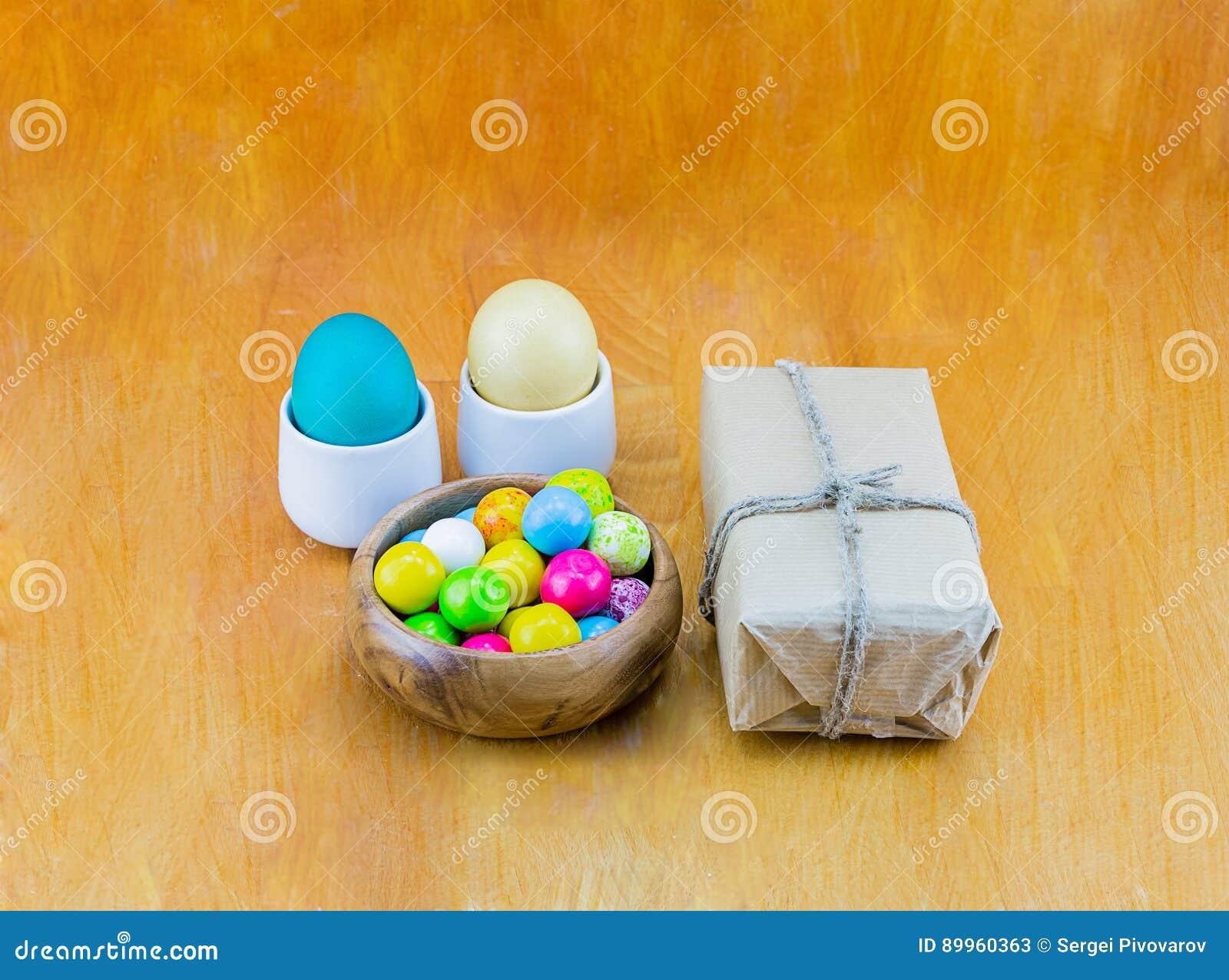 Tuggummi för pastellfärgad färg för ägg sött i en träbunke och gåva i kraft papper på en trätabellbakgrund