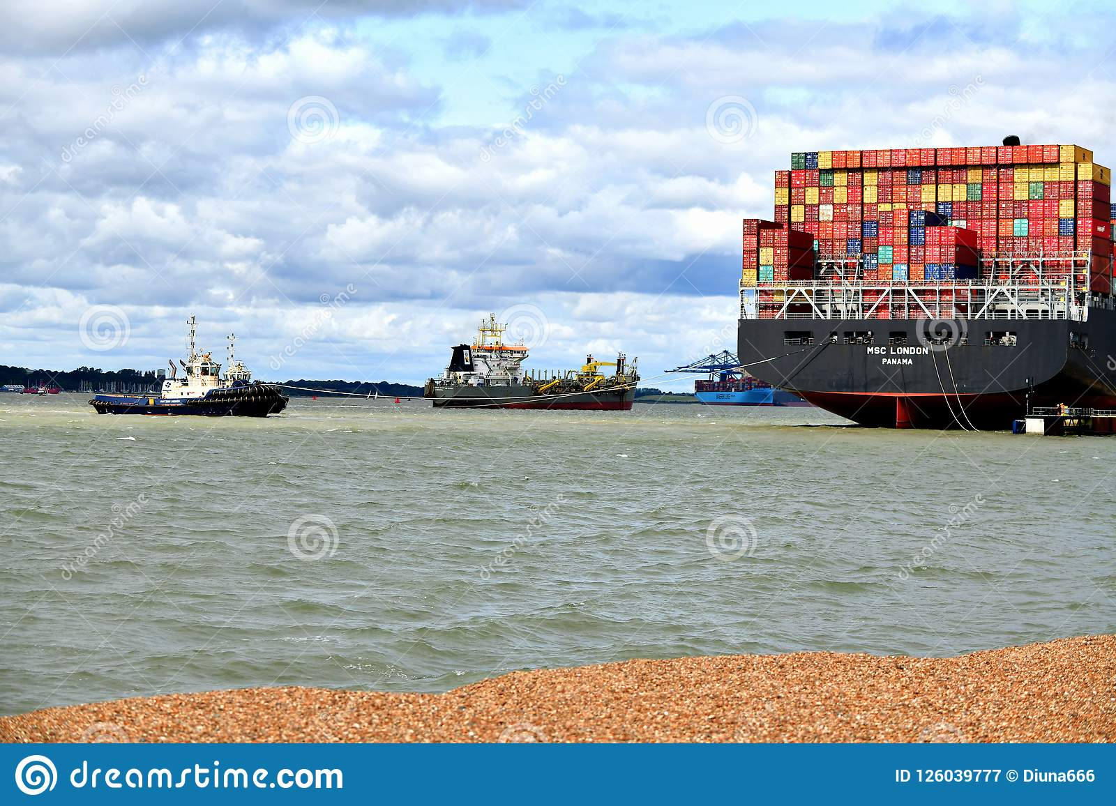 Tugs lead out a container ship from the port from Felixstowe UK