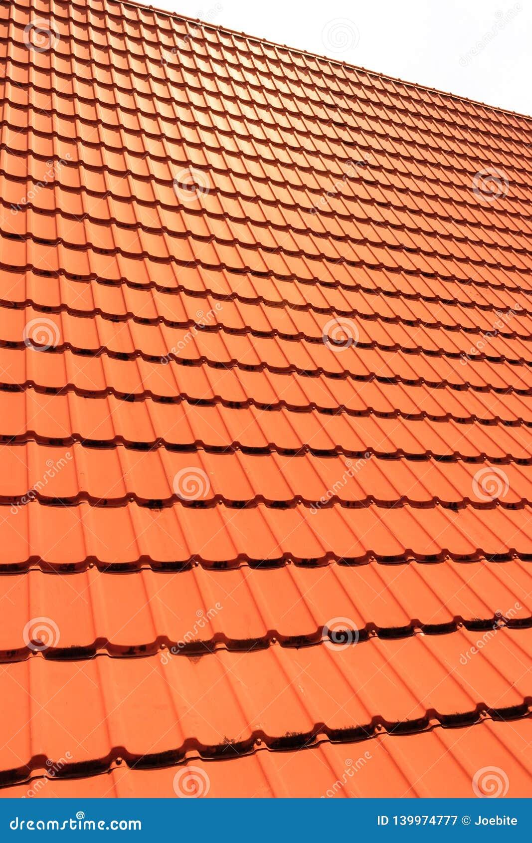 Tuiles de toit concrètes oranges sur une maison résidentielle Texture de fond de tuiles de toit