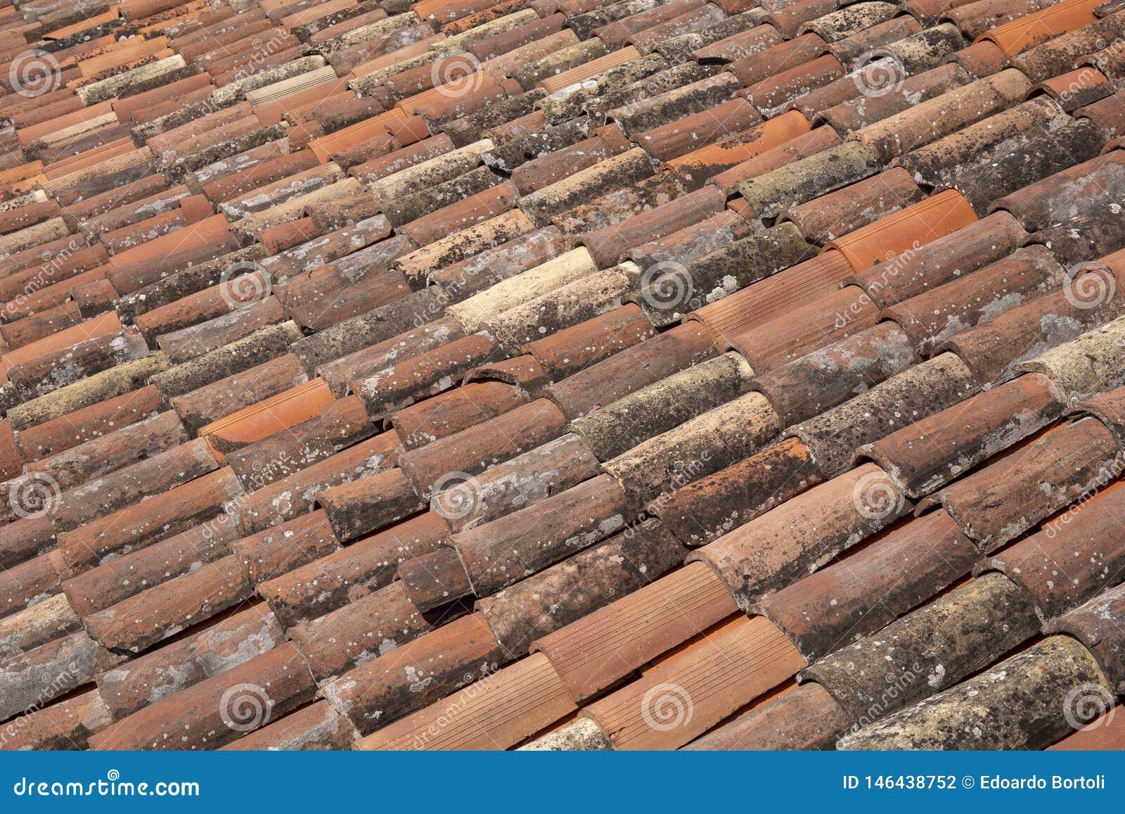 Tuiles rouges et vieilles sur un toit