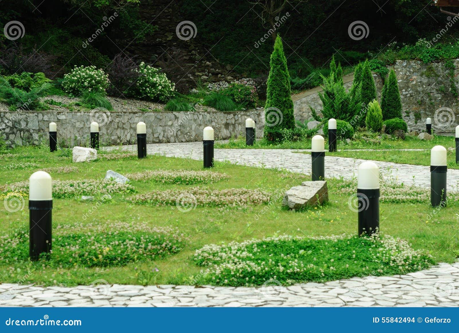 Tuin met gras, struiken en lampen