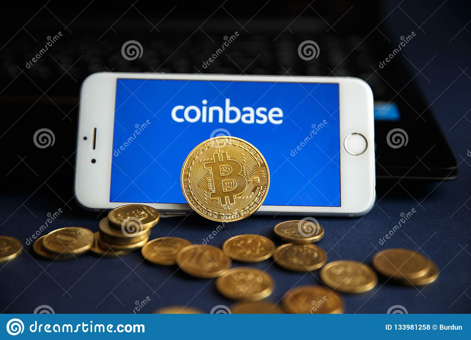Tula, Russia - August 28, 2018 Bitcoin BTC on stack of cryptocurrencies with Coinbase logo in background. The