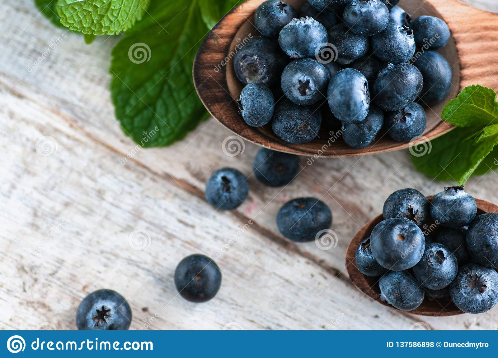 Blueberries and various forest fruits, raspberries, strawberries. There are different types of wood on the table.