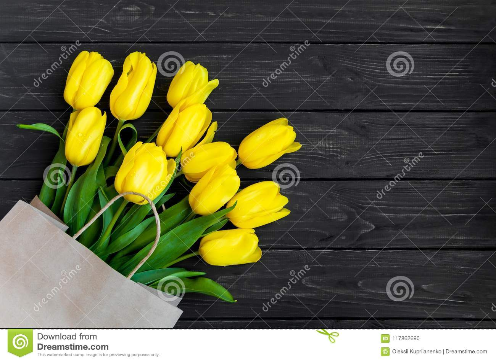Tulipanes amarillos brillantes en bolsa de papel del eco en la tabla de madera del vintage negro Endecha plana, visión superior