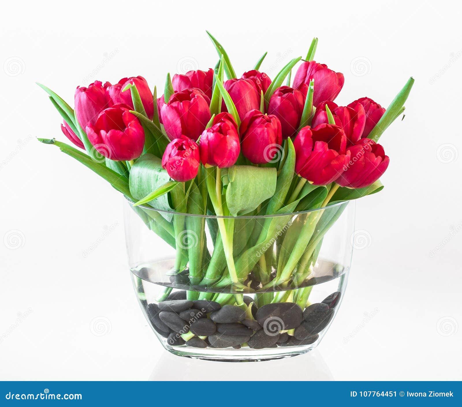 Tulipanes rojos hermosos en un florero de cristal